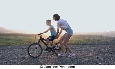 été, femme, apprend, vélo, elle, famille, jeune, vacances, tient, sunrise., fils, ou, vélo, coucher soleil, mère, équitation, conduire, enseigne, cavalcade, heureux