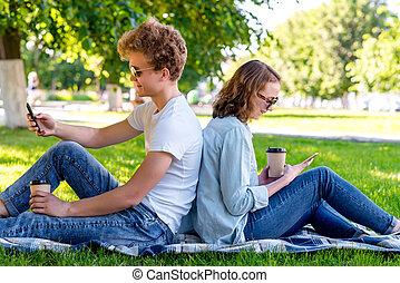 été, il, sien, hands., institute., étudiants, thé, tient, école, repos, correspondre, girl., park., regarde, social, networks., type, a, smartphone., après