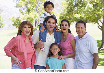 étendu famille, debout, dehors, sourire