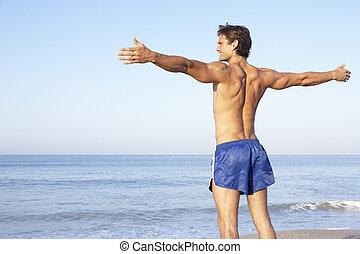 étirage, plage, jeune homme
