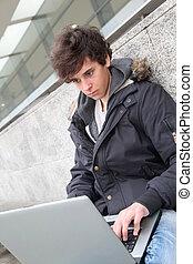 étudiant, à, ordinateur portatif, dehors, école, bâtiment