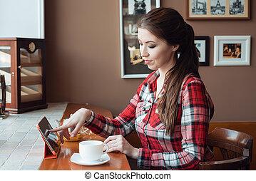 étudiant fille, dans, a, chemise plaid, dans, les, après-midi, dans, a, café, à, a, table, à, a, grande tasse, de, tea., table, les, tablette, selects, sur, les, toucher, screen., a, brunette, femme, marques, une, ordre, sur, les, internet.