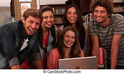 étudiants, debout, heureux, bibliothèque