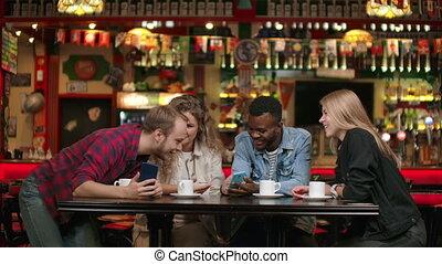étudiants, discuss., montre, africaine, écrans, amis, photos, européen, regard, parler, rire, groupe multi-ethnique, téléphone, trois, américain