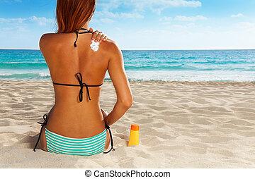 Ð¡ute girl sitting on sandy beach applying sunscreen on her back