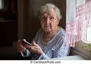 öregedő woman, noha, egy, smartphone, alatt, home.