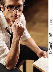 över, tänkande, story., stilig, ung man, in, glasögon, sittande, på, den, stol, med, a, bok, in, hans, hand