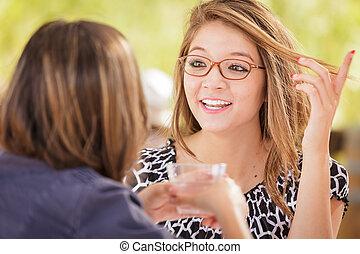 över, två, flickvänner, talande, lopp, utomhus, blandade drinkar