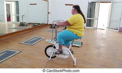 übergewichtige frau, trainieren, auf, fahrrad, simulator