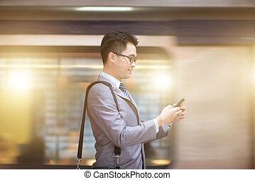 üzletember, használ, smartphone, -ban, aluljáró, station.