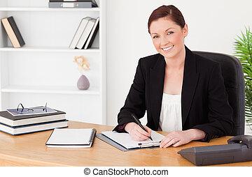 ładny, miedzianowłosa kobieta, w, garnitur, pisanie, na, niejaki, notatnik