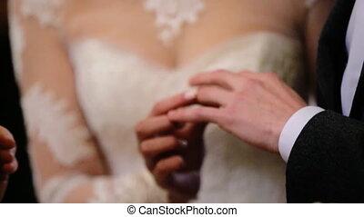 śliczny, piękny, panna młoda, chodząc, modny, biały ślub, strój, kłaść, złote kolisko, na, niejaki, palec, od, niejaki, młody, szambelan królewski, w, czarnoskóry, suit.