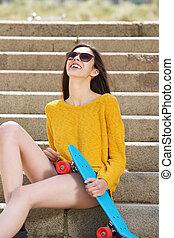 śmiech, młoda kobieta, posiedzenie na kroczy, z, skateboard