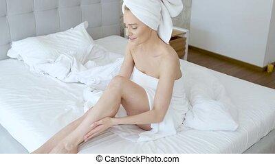 średni niemłody, piękny, blond, kobieta, moisturizes, nogi,...