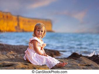 šikovný, holčička, seděn oproti vytáhnout loď na břeh, v, západ slunce