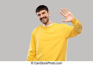 żółty, falować, ręka, człowiek, sweatshirt, młody, uśmiechanie się