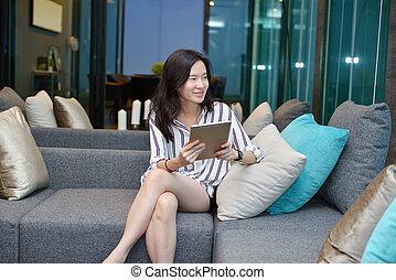 żyjący, kobieta, tabliczka, handlowy, sofa, asian, używając, przypadkowy, pokój