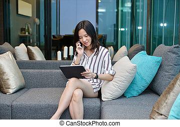 żyjący, kobieta, tabliczka, handlowy, sofa, telefonowanie, asian, używając, przypadkowy, pokój