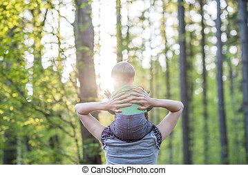 αντίκρυσμα του θηράματος από πίσω , από , ένα , νέος , μητέρα , περίπατος , με , αυτήν , βρέφος γιος , μέσα , ένα , όμορφος , φύση
