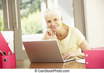 ανώτερος γυναίκα , δουλεία χρήσεως laptop , στο σπίτι