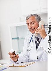 γιατρός , κράτημα , ένα , ναρκωτικό , κουτί , και , ένα , τηλέφωνο