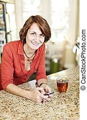 γυναίκα , χρησιμοποιώνταs , κινητό τηλέφωνο , στο σπίτι