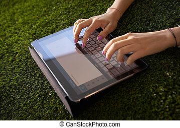 γυναίκα , emailing , και , texting , με , δισκίο , ηλεκτρονικός υπολογιστής , επάνω , γρασίδι