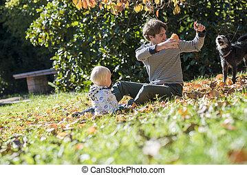 δικός του , κάθονται , φύλλα , πατέραs , νέος , παίξιμο , φθινόπωρο , παιδί , γρασίδι , γεμάτος χρώμα , μπόμπιραs