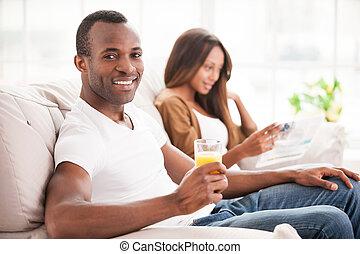 δικό τουs , ελεύθερος , γυναίκα , κάθονται , αφρικανός , γυαλί , κράτημα , ωραία , ώρα , καναπέs , ανάμιξη , δίπλα. , χυμόs , νέος , δικός του , χρόνος , πορτοκαλέα φόντο , άντραs , απολαμβάνω