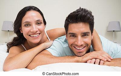 ζευγάρι , κρεβάτι , φωτογραφηκή μηχανή , ελκυστικός , χαμογελαστά , κειμένος