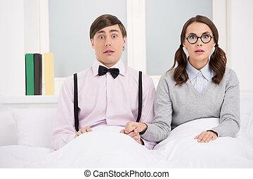 κάθονται , ζευγάρι , ανδρόγυνο. , κρεβάτι , ατενίζω , φωτογραφηκή μηχανή , nerd , έκπληκτος