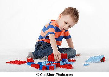 μικρό αγόρι , παίξιμο , με , σχεδιαστής , στο πάτωμα