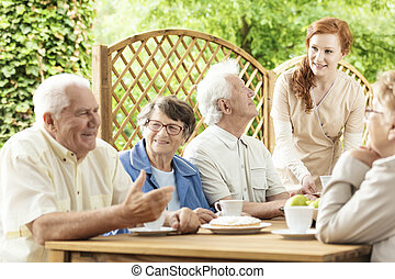 σύνολο , από , ηλικιωμένος , συνταξιούχος , απολαμβάνω , δικό τουs , ώρα , μαζί , από , ένα , τραπέζι , έξω , μέσα , ένα , κήπος , από , ένα , συνταξιοδότηση , home., νέος , επιστάτης , assisting.