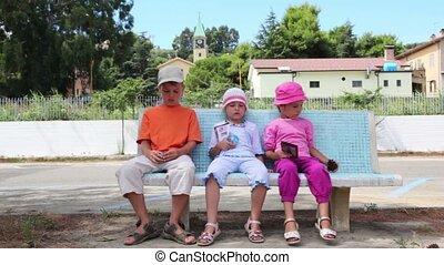 τρία παιδιά , κάθονται , αναμμένος άρθρο πάγκος