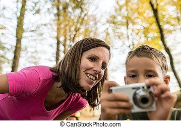 χαμογελαστά , μητέρα , looking at , ένα , εικόνα , επάνω , ένα , φωτογραφηκή μηχανή , αόρ. του hold , από , αυτήν , νέος , υιόs