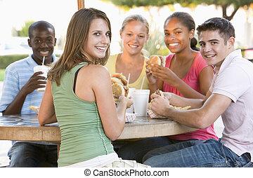 группа, of, teenagers, сидящий, на открытом воздухе, принимать пищу, быстро, питание