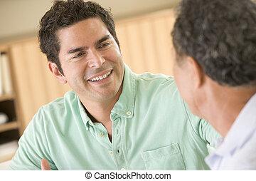 два, люди, сидящий, в, гостиная, talking, and, улыбается