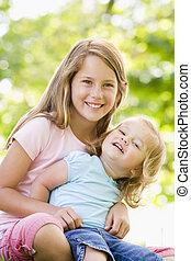 два, sisters, сидящий, на открытом воздухе, улыбается