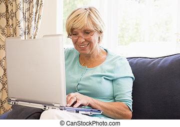 женщина, в, гостиная, with, портативный компьютер, улыбается