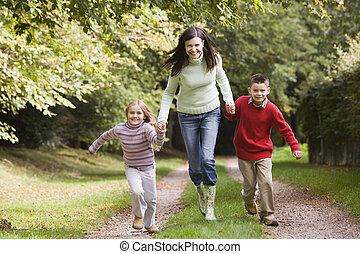 женщина, на открытом воздухе, with, два, молодой, children, гулять пешком, на, дорожка, держа, руки, and, улыбается, (selective, focus)