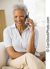 женщина, сидящий, в, гостиная, с помощью, телефон, and, улыбается