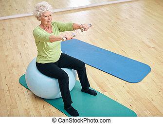 женщина, сидящий, exercising, мяч, dumbbells, старшая