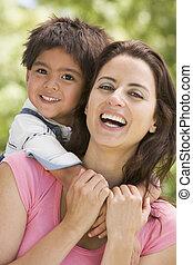 женщина, and, молодой, мальчик, embracing, на открытом воздухе, улыбается