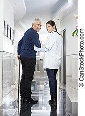 задний, посмотреть, of, женский пол, врач, гулять пешком, with, старшая, пациент