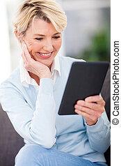 зрелый, женщина, чтение, , книга, на, таблетка, компьютер