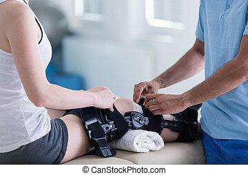 крупный план, на, человек, with, подкрепляющий, на, сломанный, нога, в течение, реабилитация, with, физиотерапевт