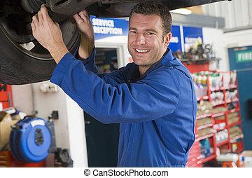 механик, за работой, под, автомобиль, улыбается