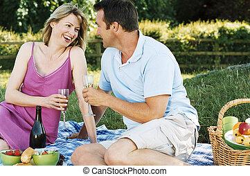пара, сидящий, на открытом воздухе, with, пикник, улыбается