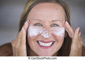 радостный, зрелый, женщина, лицо, кремовый, уход за кожей