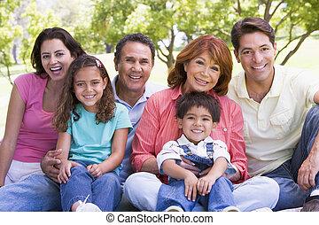 расширенный, семья, сидящий, на открытом воздухе, улыбается